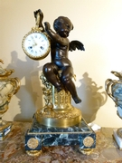 A gilded and patinated bronze clock with a cherub on a green marble base.