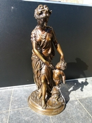 A bronze patinated sculpture of a lady with a putto.